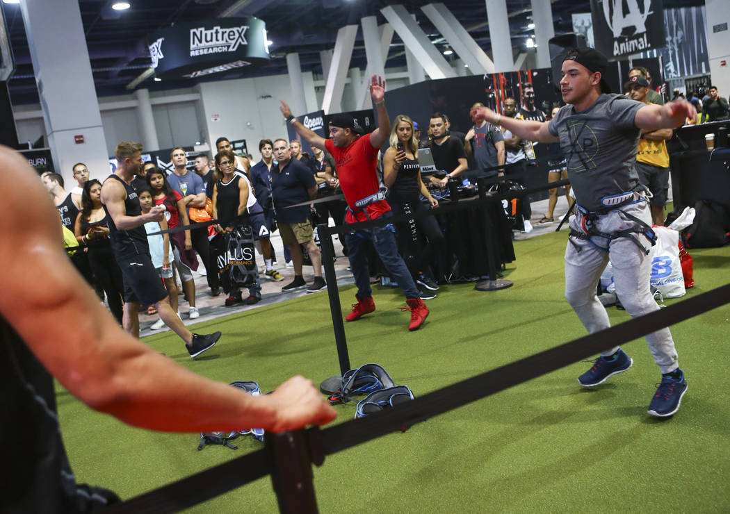 Steve McIntyre, center, and Rafael Marin, both of Las Vegas, compete in a challenge course at the Performix booth during Joe Weider's Olympia's Fitness & Performance Expo at the Las Vegas Conv ...