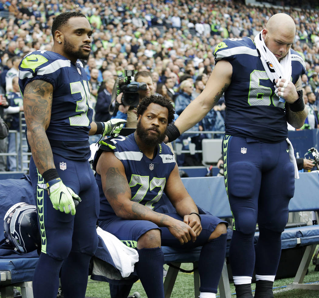 Seattle Seahawks defensive end Michael Bennett, center, is joined by teammates Thomas Rawls, left, and Justin Britt, right, as he sits during the singing of the national anthem before an NFL footb ...