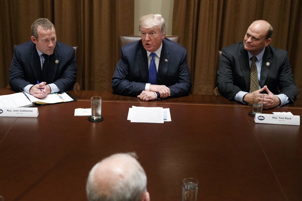 Rep. Josh Gottheimer, D-N.J., left, and Rep. Tom Reed, R-N.Y., right, listen as President Donald Trump speaks during a meeting with a bipartisan group of lawmakers in the Cabinet Room of the White ...