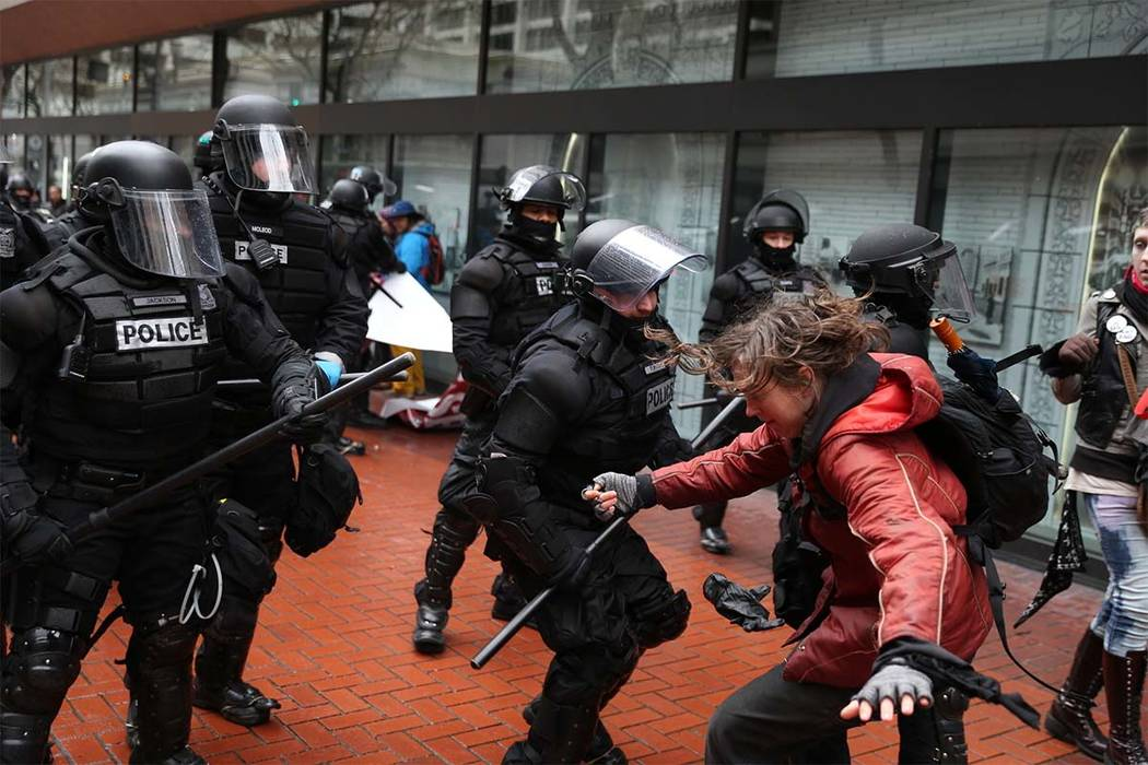 In this Feb. 20, 2017 file photo,m protesters clash with police, in Portland, Oregon. Trump supporters and left-wing protesters have taken to the streets repeatedly in recent months in supposed fr ...