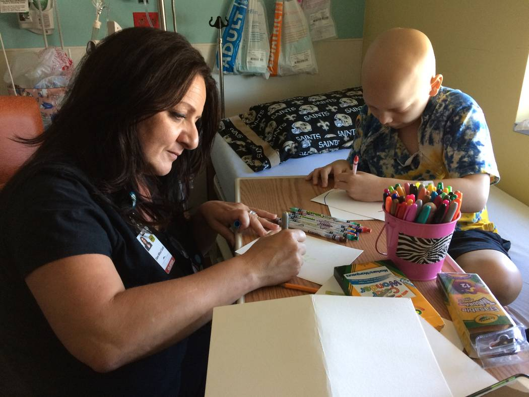 Diane Mifsud does her own art as Cole Thow, 10, works his project Aug. 18, 2017, at Summerlin Hospital. She often introduces herself the Fairy Art Princess, which brings a smile to the children' ...