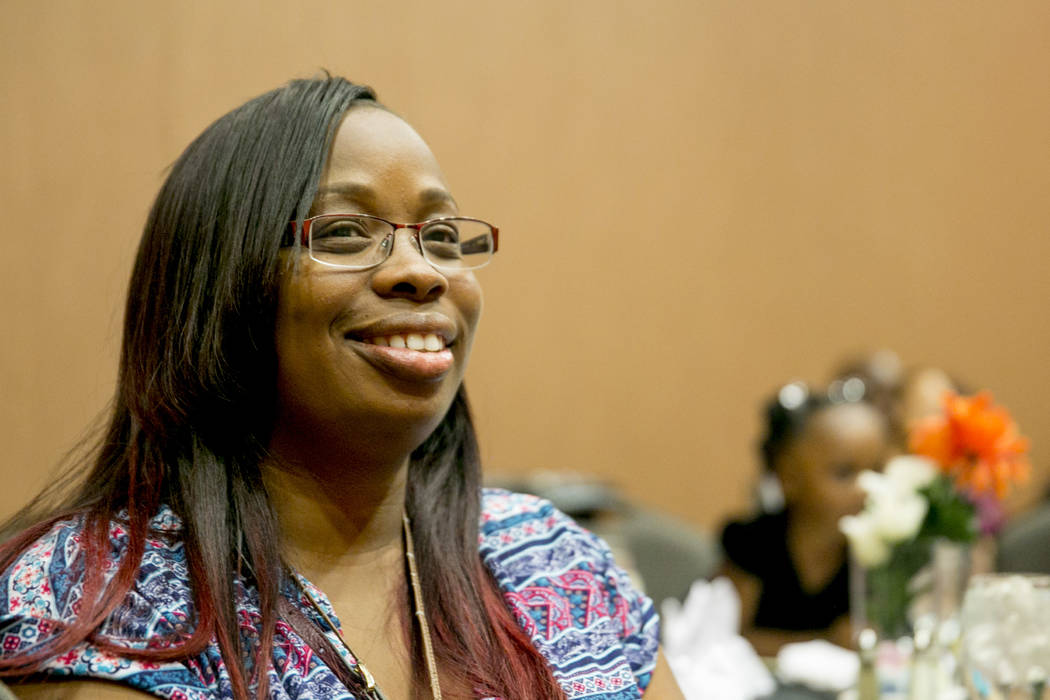 Taquana Edwards, 35, a graduate of the Family Self-Sufficiency Program, smiles while listening to a speaker during the Southern Nevada Regional Housing Authority's Family Self-Sufficiency Program  ...