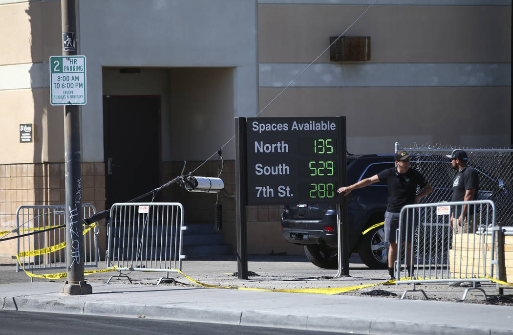 People look at a power line that was knocked down by a heavy equipment vehicle along Stewart Avenue between 6th and 7th Streets in downtown Las Vegas as setup for the Life is Beautiful festival go ...