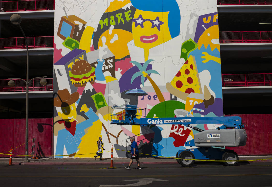 Pedestrians pass by a mural in progress by Greek street artist b. ahead of the Life is Beautiful festival in downtown Las Vegas on Thursday, Sept. 14, 2017. Chase Stevens Las Vegas Review-Journal  ...