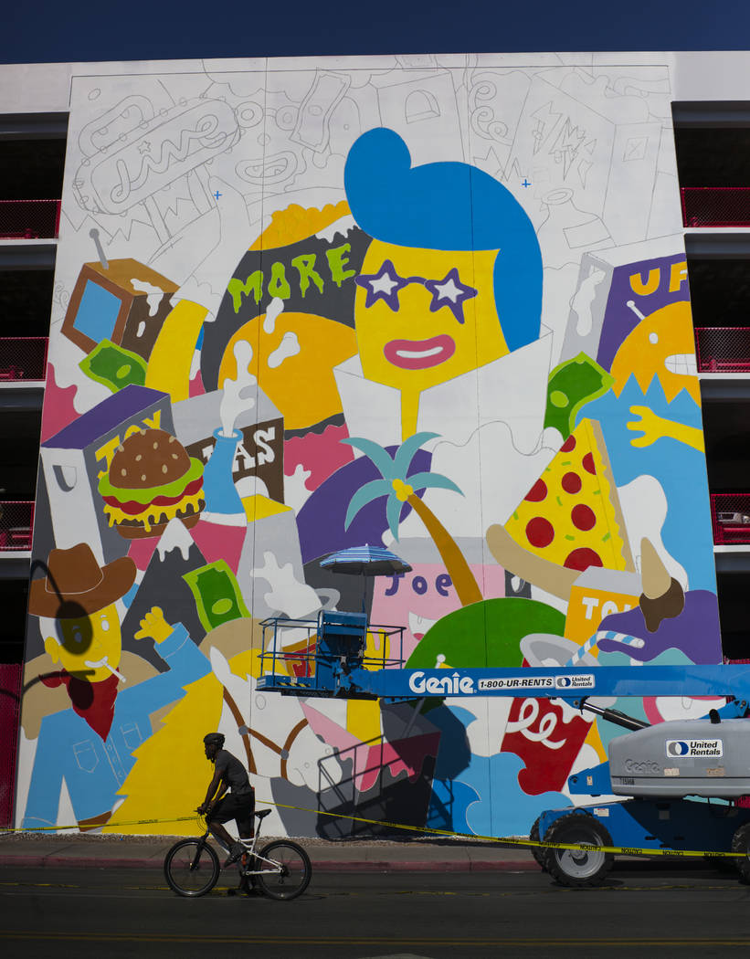 A bicyclist passes by a mural in progress by Greek street artist b. ahead of the Life is Beautiful festival in downtown Las Vegas on Thursday, Sept. 14, 2017. Chase Stevens Las Vegas Review-Journa ...