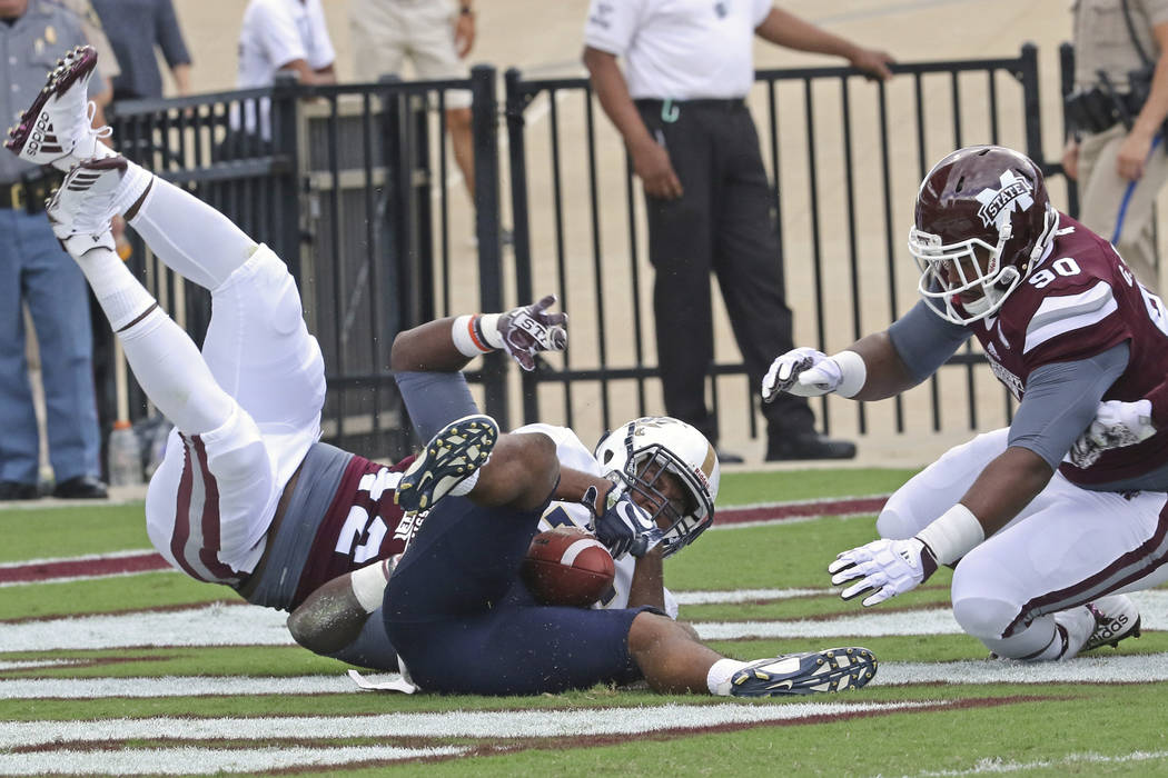 Mississippi State defensive lineman Marquiss Spencer (42) is upended and downs Charleston Southern running back Chanin Hamilton (25) in the end zone for a safety as Mississippi State defensive bac ...