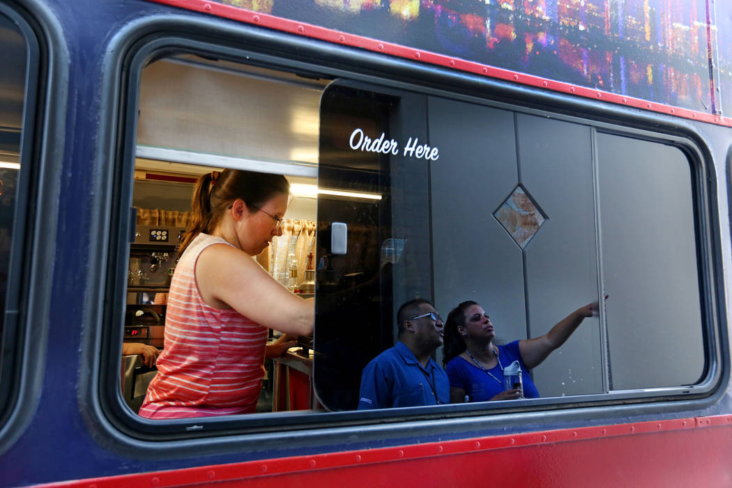 Barista Leah Koepp, left, works while Virgil Rayos, center, and Judy Sundin with The United States Postal Service, choose their speciality coffee from Art Bus Coffee, a mobile double decker bus th ...