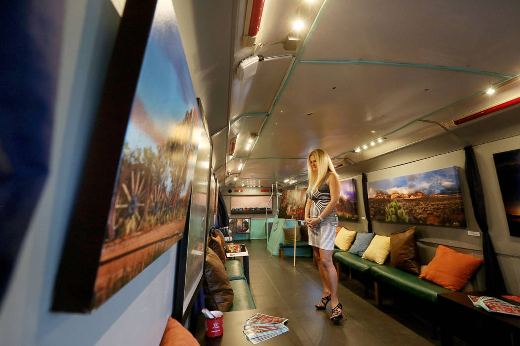 Owner and director of operations for Mailmax Mailing Solutions Mary Soto looks at artwork by Steve Patchin in Art Bus Coffee, a mobile double decker bus that acts as both an art gallery and a coff ...