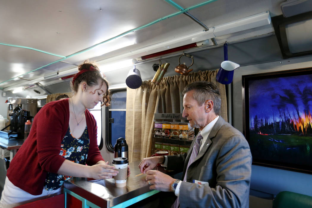 Barista Athena Patchin serves district sales manager for Riso David Nutter in the Art Bus Coffee, a mobile double decker bus that acts as both an art gallery and a coffee shop, serving outside of  ...