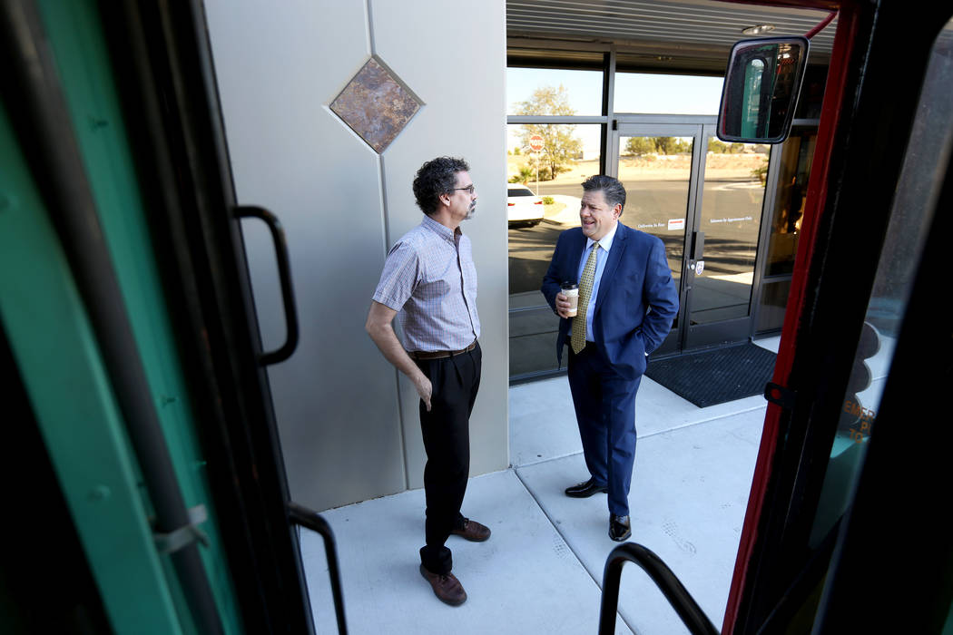 Artist and owner of Art Bus Coffee Steve Patchin, left, speaks with owner of Mailmax Mailing Solutions Francisco Soto by the mobile double decker bus that acts as both an art gallery and a coffee  ...