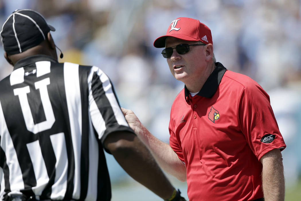 Louisville head coach Bobby Petrino speaks with an official during the first half of an NCAA college football game against North Carolina in Chapel Hill, N.C., Saturday, Sept. 9, 2017. (AP Photo/G ...