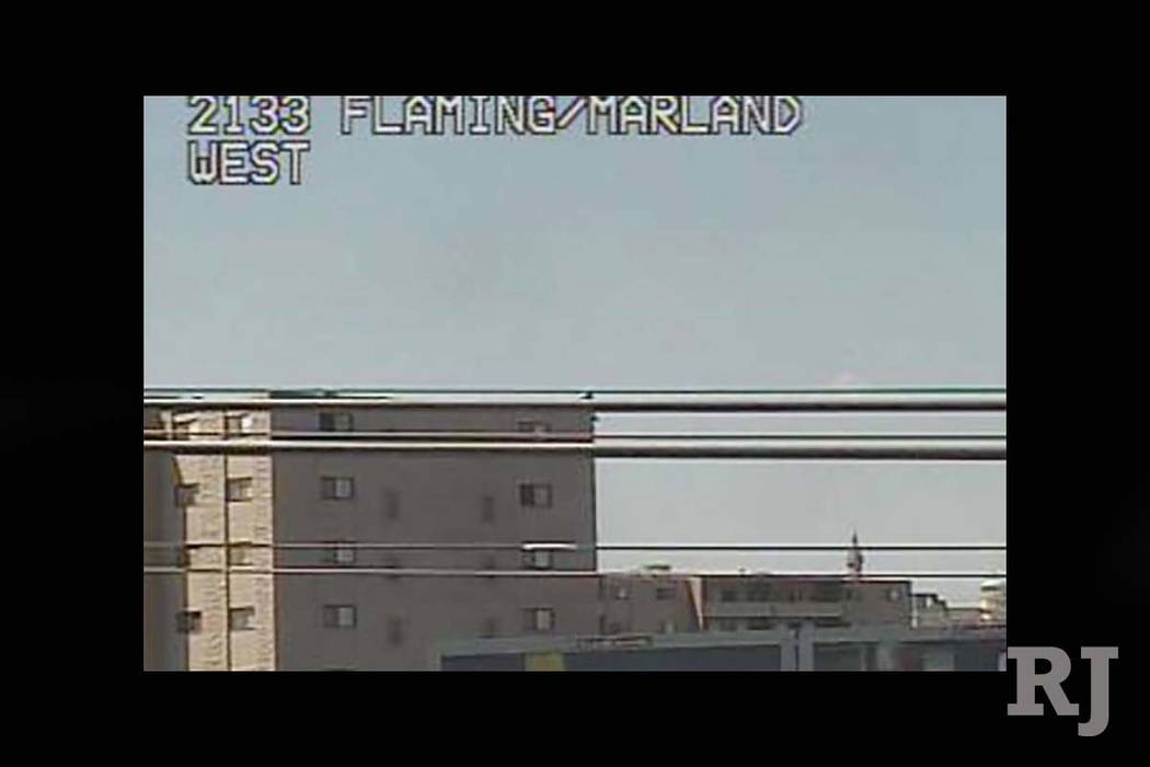 A man is perched on the edge of the roof of an apartment building near Flamingo Road and Maryland Parkway, threatening to jump, Thursday, Sept. 13, 2017. (RTC FAST Cameras)