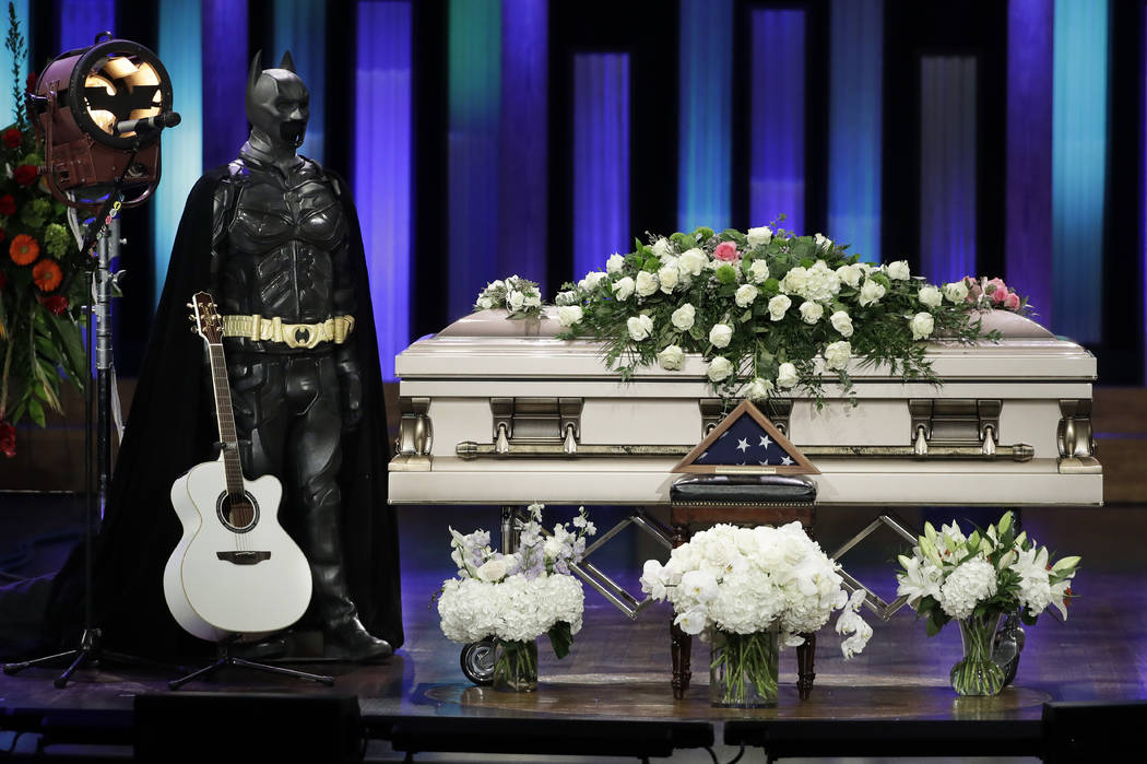 A Batman costume and guitar stand next to the casket during a memorial service for country music singer Troy Gentry at the Grand Ole Opry House Thursday, Sept. 14, 2017, in Nashville, Tenn. Gentry ...