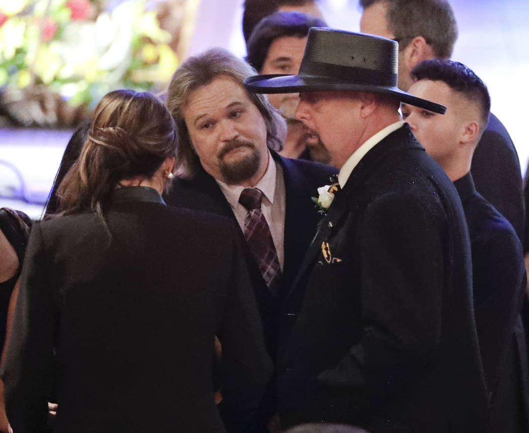 Eddie Montgomery, foreground right, talks with fellow country music singer Travis Tritt, center, before a memorial service for Troy Gentry at the Grand Ole Opry House Thursday, Sept. 14, 2017, in  ...