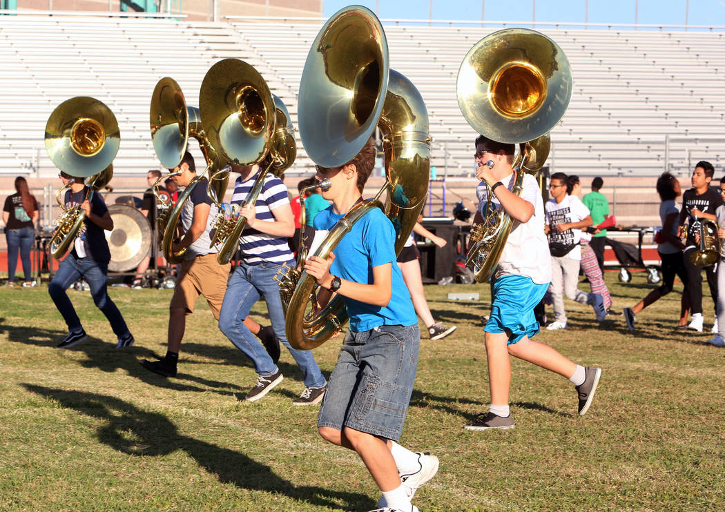 The Silverado High School marching band sousaphone players, including Dante Chandler, center, Hunter Ballinger, right, and Connor Hendrix, third left, run to take their positions during practice o ...