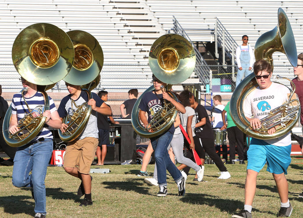 The Silverado High School marching band sousaphone players, including Connor Hendrix, left, and Hunter Ballinger, right, run to take their positions during practice on Thursday, Sept. 14, 2017, in ...