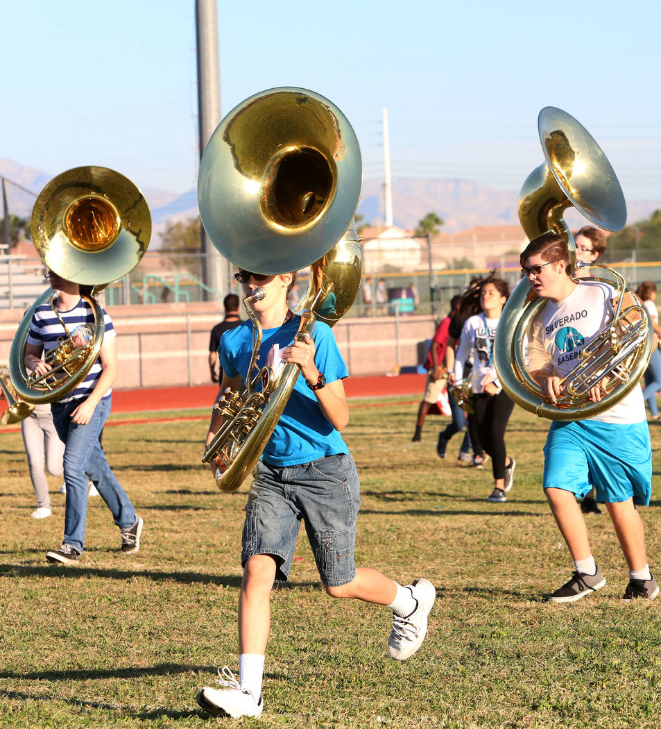 The Silverado High School marching band sousaphone players Connor Hendrix, left, Dante Chandler and Hunter Ballinger, right, run to take their positions during practice on Thursday, Sept. 14, 2017 ...
