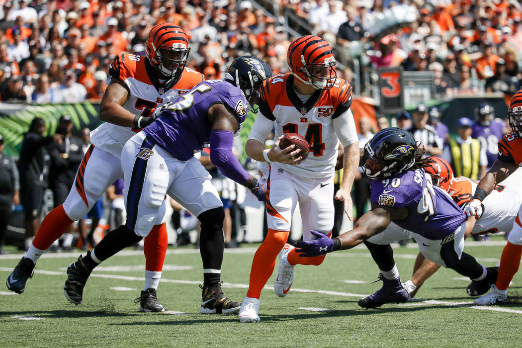 Cincinnati Bengals quarterback Andy Dalton (14) is sacked by Baltimore Ravens outside linebacker Za'Darius Smith (90) in the first half of an NFL football game, Sunday, Sept. 10, 2017, in Cincinna ...