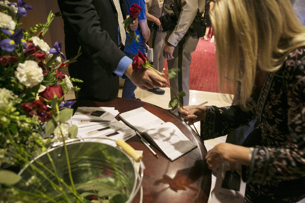 Roses are handed out to women during a memorial for Las Vegas court bailiff William Datthyn, 45, at Las Vegas City Hall Friday, Sept. 15, 2017, in Las Vegas. Datthyn was known as being a giving pe ...