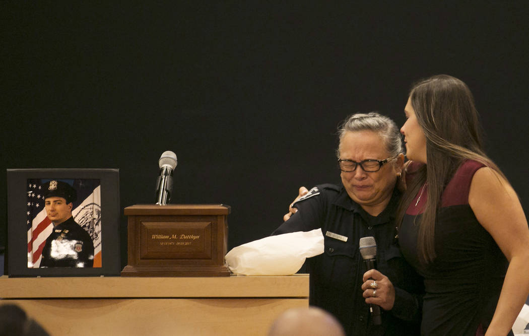"""During a memorial for Las Vegas court bailiff William Datthyn, 45, marshal Trina Bryant sings """"Amazing Grace"""" while being comforted by Datthyn's sister, Desiree Barber, at Las Ve ..."""