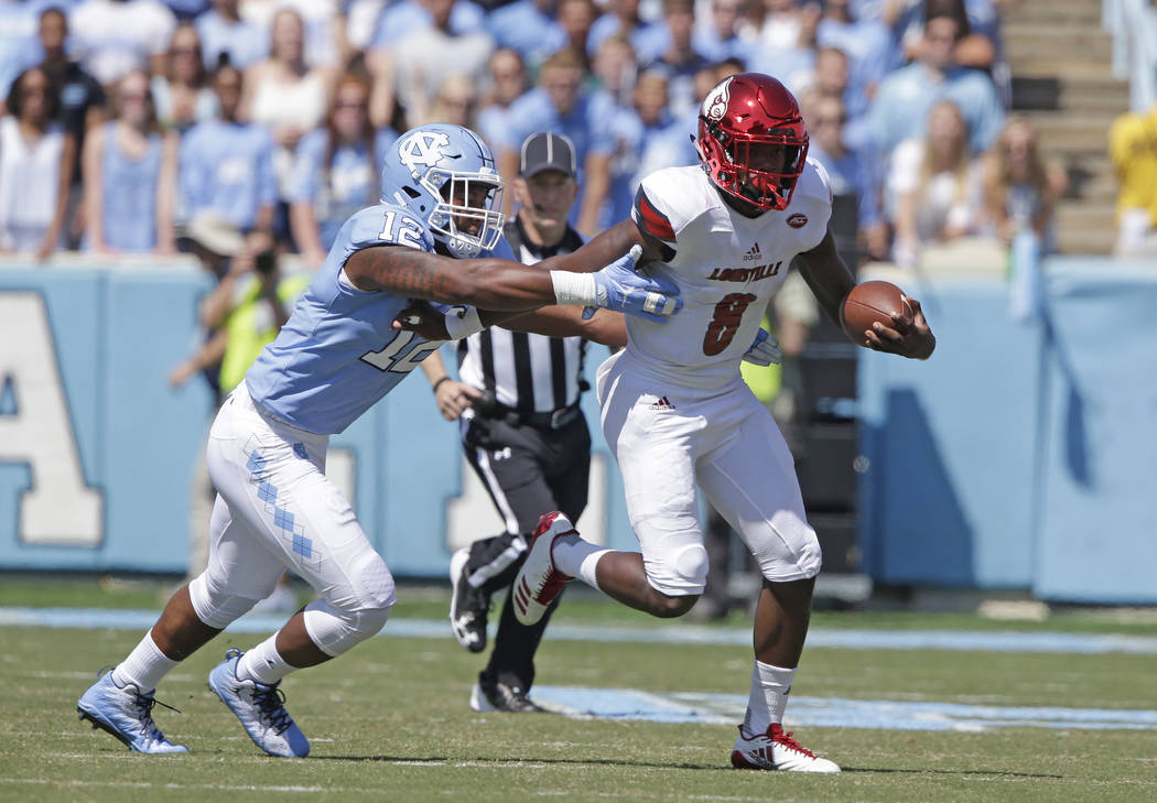 Louisville quarterback Lamar Jackson (8) runs the ball as North Carolina's Tomon Fox (12) chases during the first half of an NCAA college football game in Chapel Hill, N.C., Saturday, Sept. 9, 201 ...