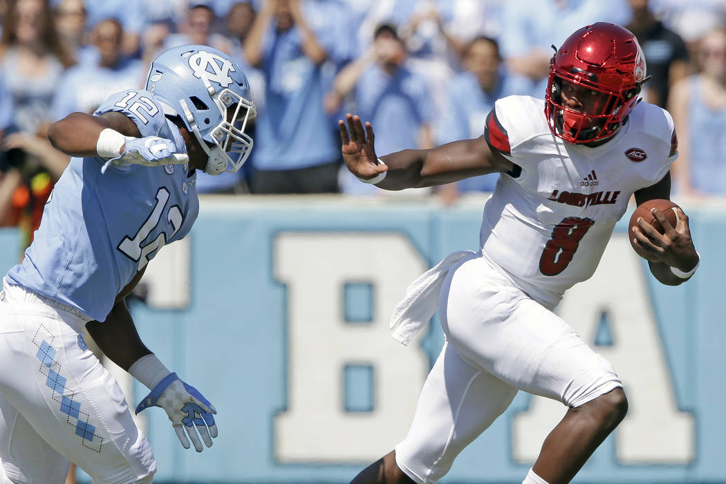 FILE - In this Sept. 9, 2017, file photo, Louisville quarterback Lamar Jackson (8) runs the ball as North Carolina's Tomon Fox (12) chases him during the first half of an NCAA college football gam ...