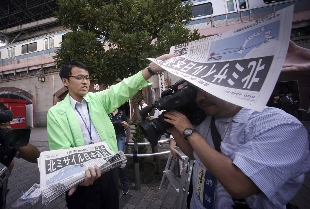 A man distributes an extra edition of a newspaper reporting about North Korea's missile launch at Shimbashi Station in Tokyo, Friday, Sept. 15, 2017. (AP Photo/Eugene Hoshiko)