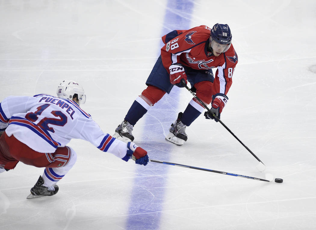 Washington Capitals defenseman Nate Schmidt (88) battles for the puck against New York Rangers left wing Matt Puempel (12) during the third period of an NHL hockey game, Wednesday, April 5, 2017,  ...