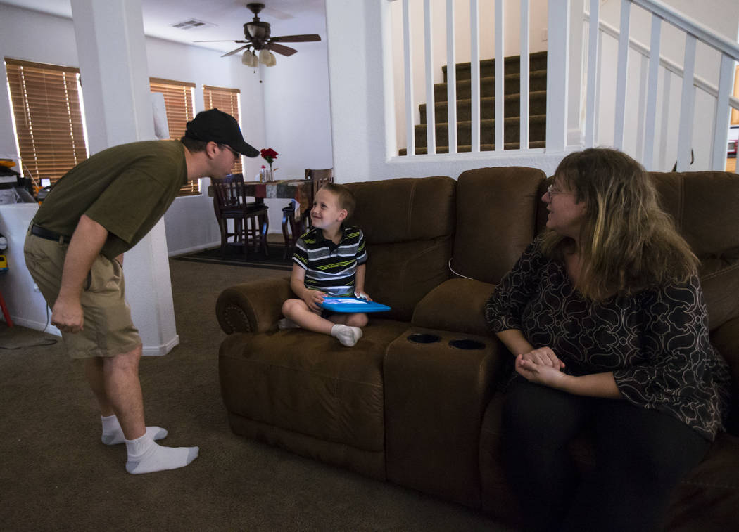 Matt Minkowsky, left, shows his son Brandon, 6, his Golden Knights hat as wife Caryn looks on at their home in northwest Las Vegas on Wednesday, Sept. 20, 2017. Matt currently has stage II brain c ...