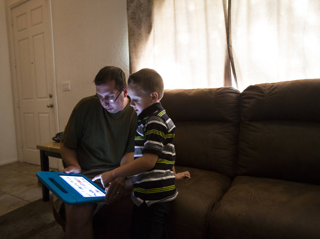 Matt Minkowsky, left, looks at an iPad with his son Brandon, 6, at their home in northwest Las Vegas on Wednesday, Sept. 20, 2017. Matt currently has stage II brain cancer, and also underwent surg ...