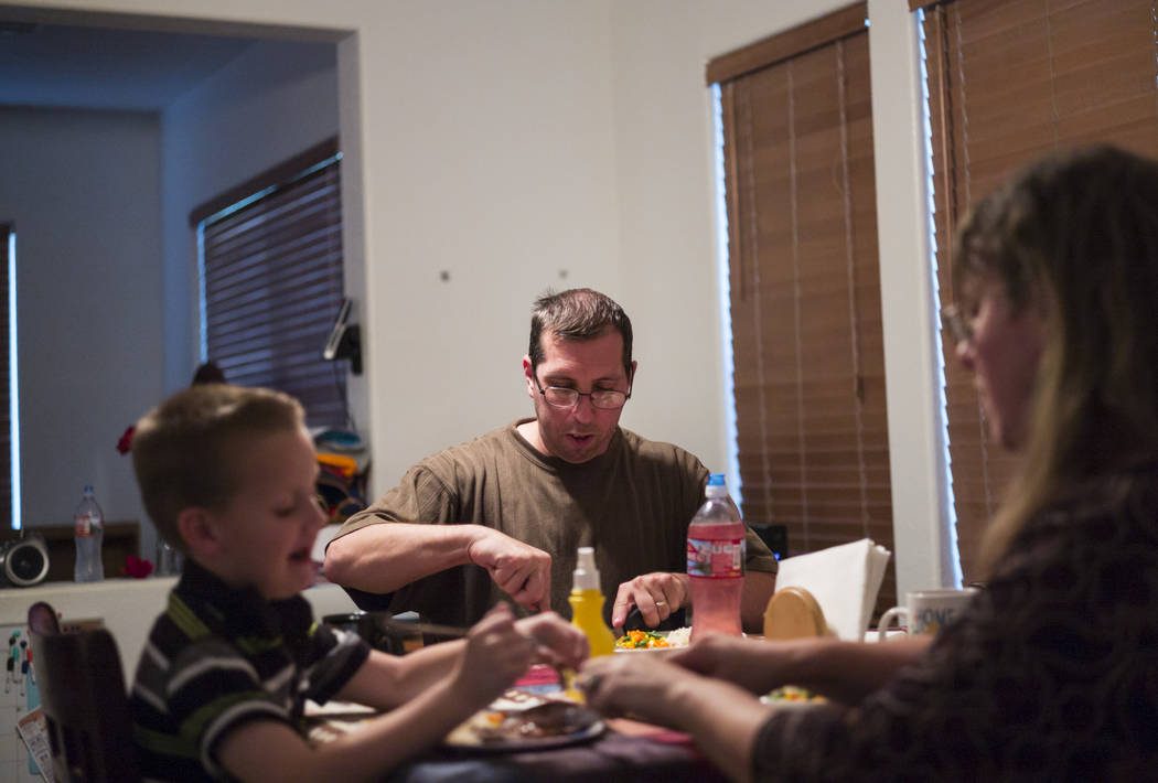 Matt Minkowsky, center, eats dinner next to his son Brandon, 6, and wife Caryn at their home in northwest Las Vegas on Wednesday, Sept. 20, 2017. Although the family receives just enough to get by ...