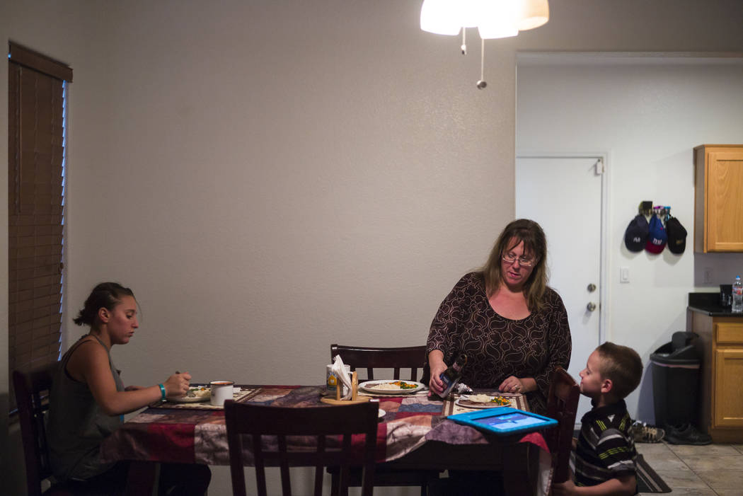 Caryn Minkowsky, center, sets the table for dinner next to her children Tiffani, 14, left, and Brandon, 6 at their home in northwest Las Vegas on Wednesday, Sept. 20, 2017. Although the family rec ...