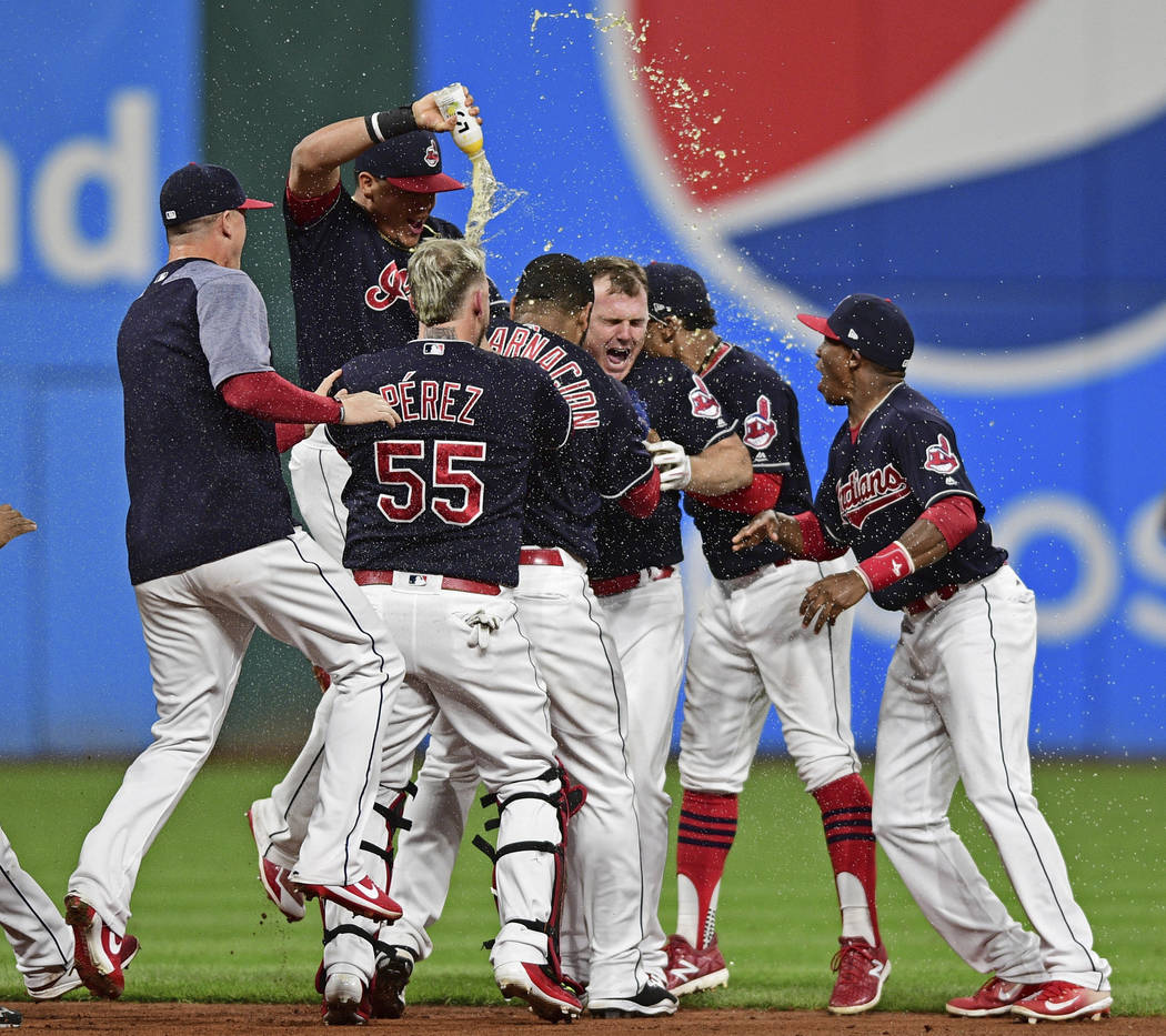 Cleveland Indians' Jay Bruce, center, celebrates with teammates after Bruce drove in the winning run with a double off Kansas City Royals relief pitcher Brandon Maurer during the 10th inning of a  ...