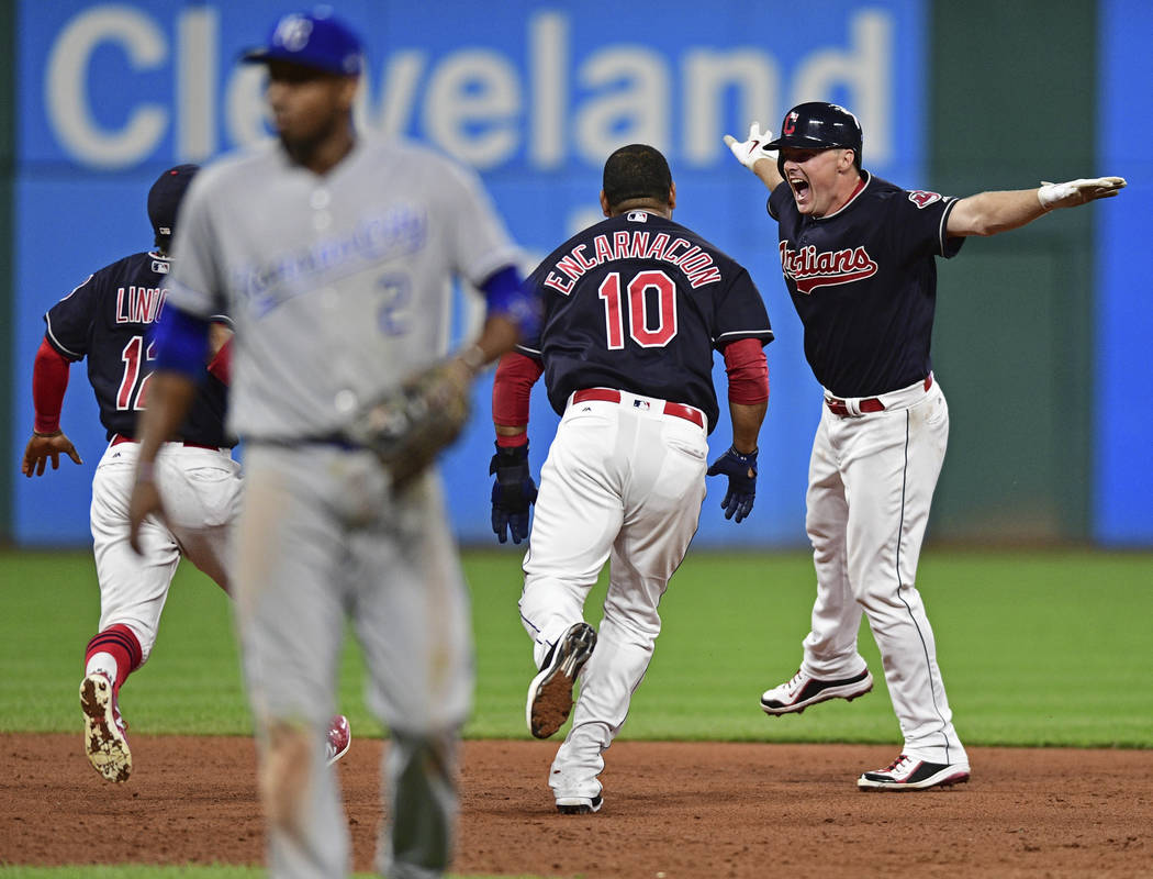 Cleveland Indians' Jay Bruce, right, celebrates with Edwin Encarnacion and Francisco Lindor celebrate after Bruce hit a double off Kansas City Royals pitcher Brandon Maurer during the 10th inning  ...