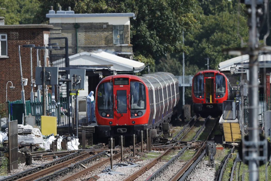 A police forensic officer stands beside the train, at left, where an incident happened, that police say they are investigating as a terrorist attack, at Parsons Green subway station in London, Fri ...