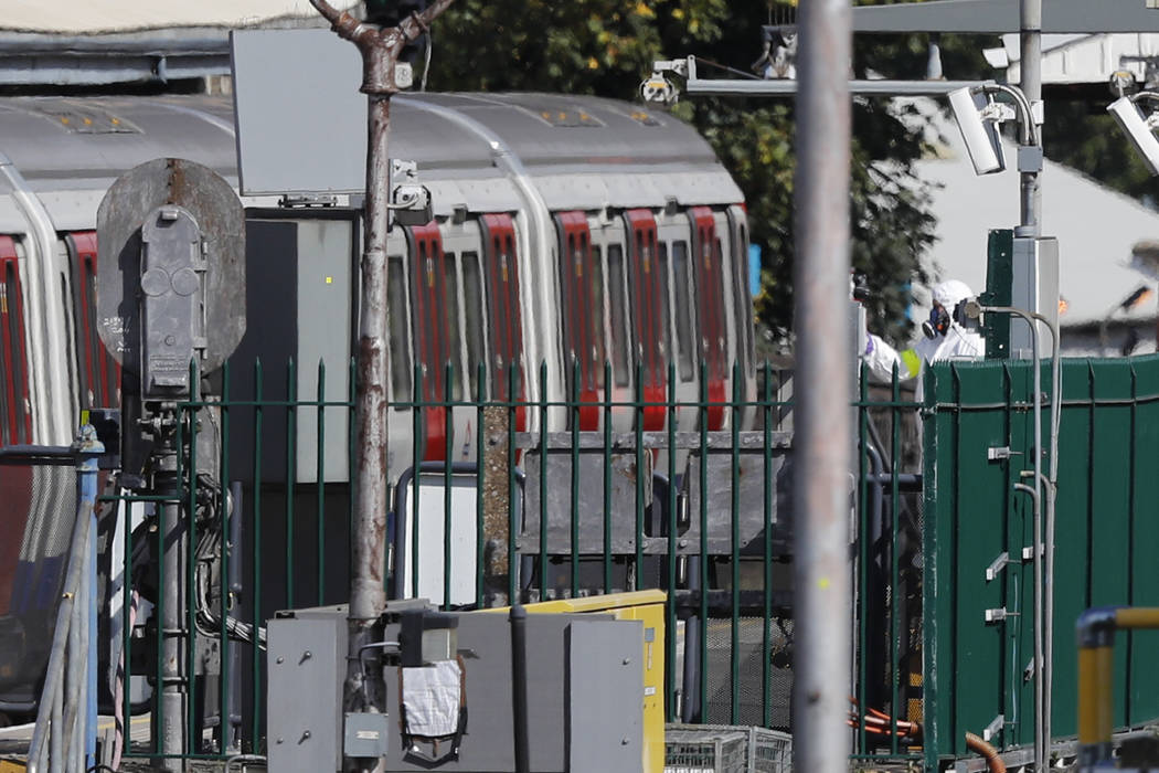 A police forensic officer stands at right near the train, at left, where an incident happened that police say they are investigating as a terrorist attack, at Parsons Green subway station in Londo ...