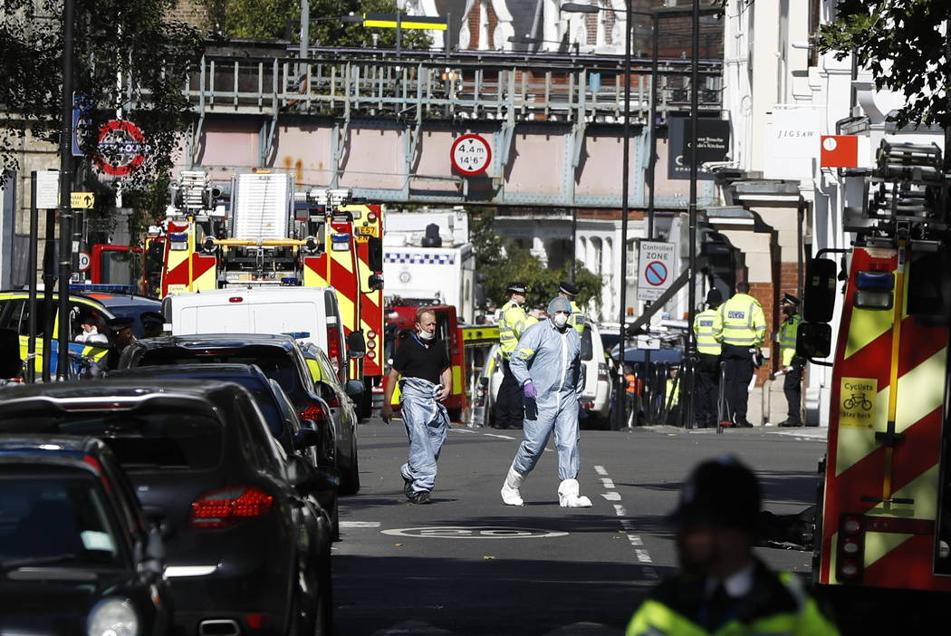 Police forensic officers walk within a cordon near where an incident happened, that police say they are investigating as a terrorist attack, at Parsons Green subway station in London, Friday, Sept ...