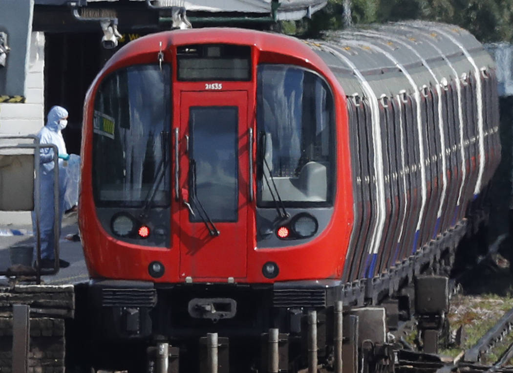 A police forensic officer stands beside the train where an incident happened, that police say they are investigating as a terrorist attack, at Parsons Green subway station in London, Friday, Sept. ...
