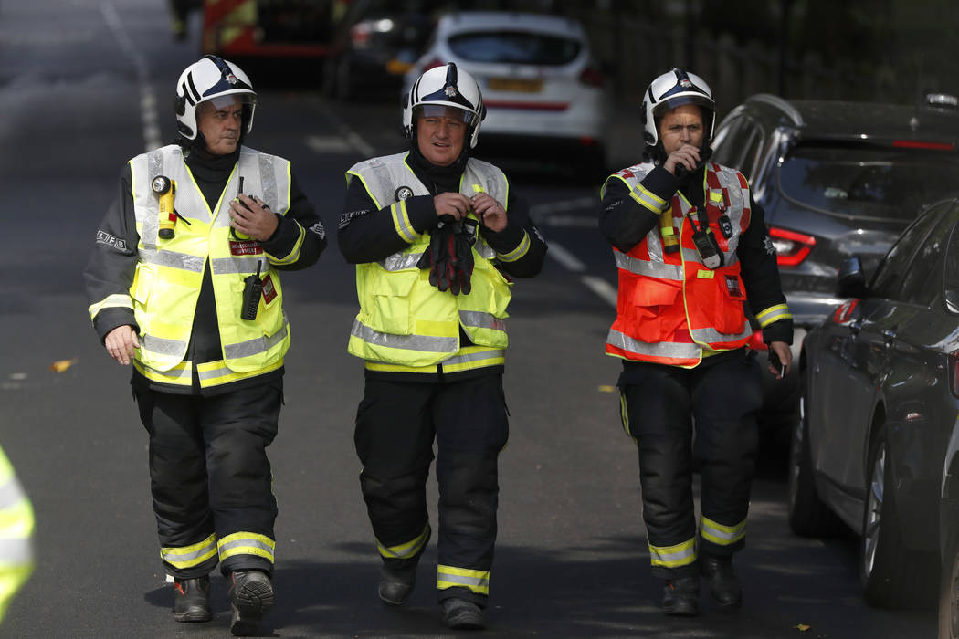 Fire brigade officers walk within a cordon near where an incident happened, that police say they are investigating as a terrorist attack, at Parsons Green subway station in London, Friday, Sept. 1 ...