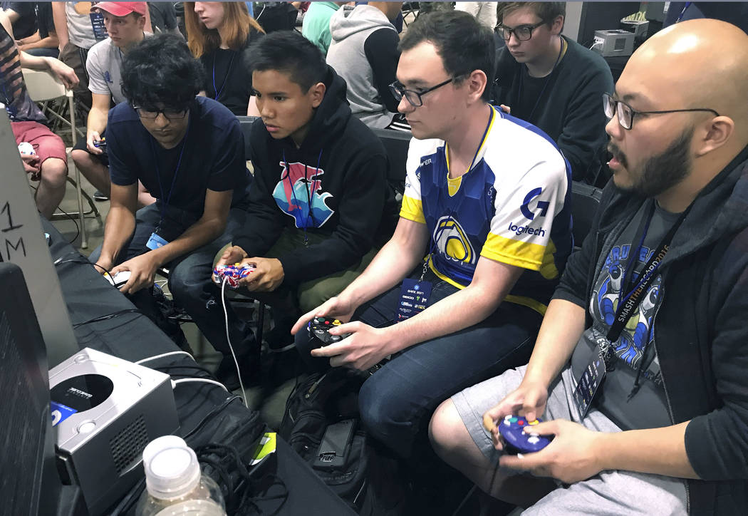 "In this Aug. 25, 2017, photo, Connor Nguyen, at right, and Griffin Williams, second from right, compete in a ""Super Smash Bros. Melee"" tournament at the Shine eSports festival at ..."