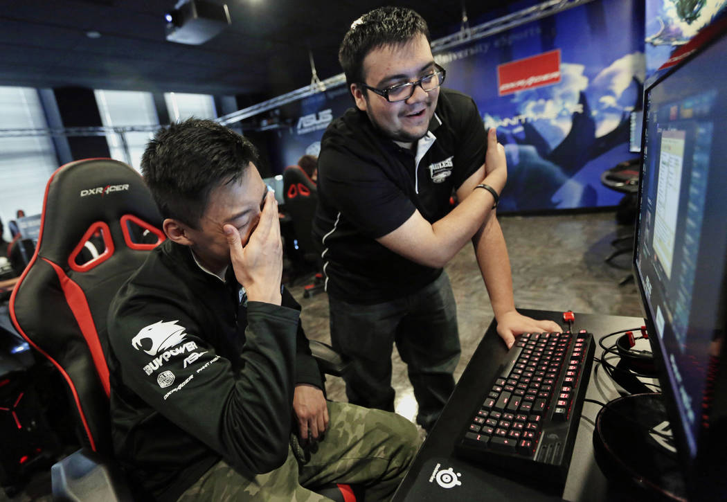 "FILE - In this Sept. 23, 2014 photo, Robert Morris University Illinois freshman, Alex Chapman, left, is critiqued by assistant coach Jose Carrasco as he practices playing the video game "" ..."