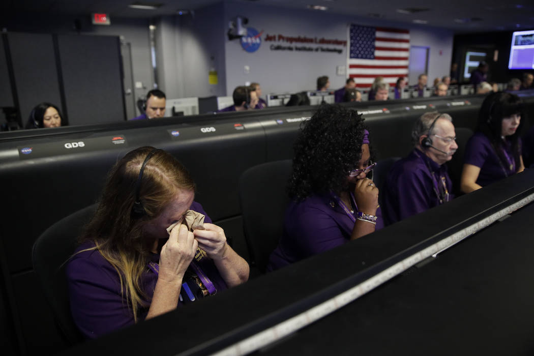 Engineer Nancy Vandermay, left, wipes her tears in mission control at NASA's Jet Propulsion Laboratory after confirmation of Cassini's demise Friday, Sept. 15, 2017, in Pasadena , Calif. Cassini d ...