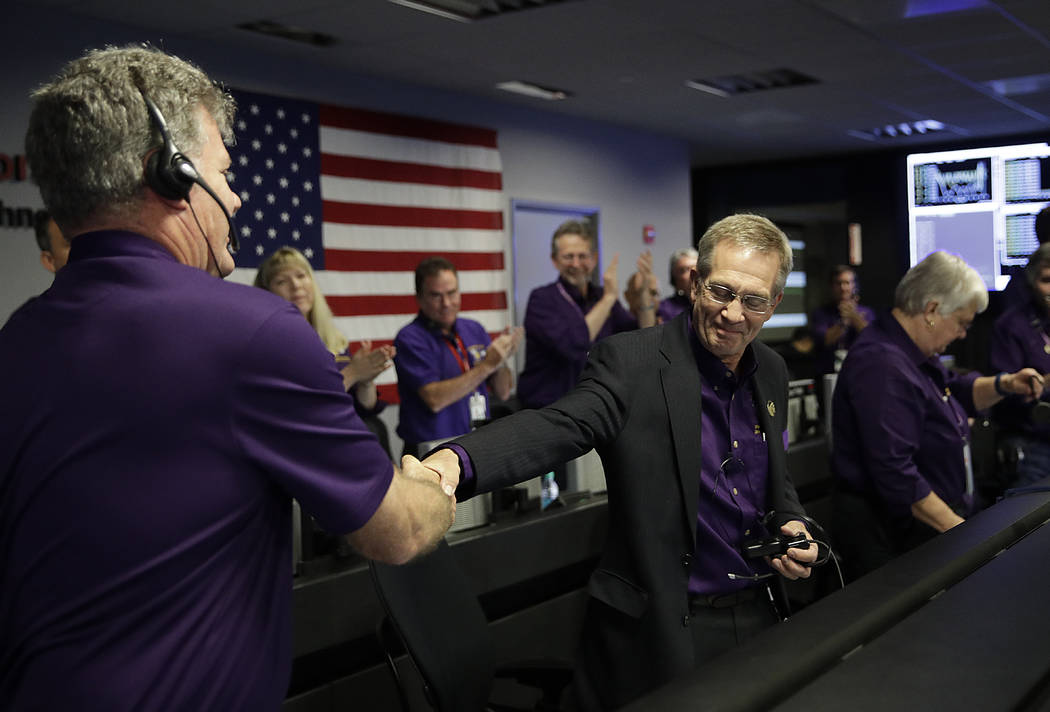 Project manager Earl Maize, center, shakes hands with Bill Heventhal in mission control at NASA's Jet Propulsion Laboratory, Friday, Sept. 15, 2017, in Pasadena, Calif. after confirmation of Cassi ...