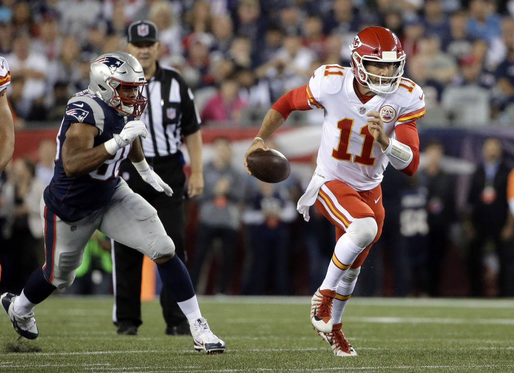 Kansas City Chiefs quarterback Alex Smith (11) scrambles from New England Patriots defensive end Trey Flowers, left, during the first half of an NFL football game, Thursday, Sept. 7, 2017, in Foxb ...