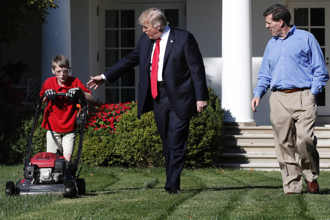 Frank Giaccio, 11, of Falls Church, Virginia, left, is accompanied by President Donald Trump as he mows the lawn of the Rose Garden, Friday, Sept. 15, 2017, at the White House in Washington, with  ...