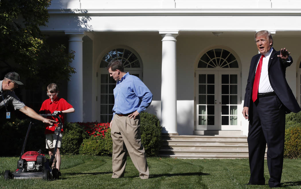 Frank Giaccio, 11, of Falls Church, Virginia, left, is assisted by a member of the National Park Service, and his father Greg Giaccio, as he gets back to mowing the lawn after President Donald Tru ...