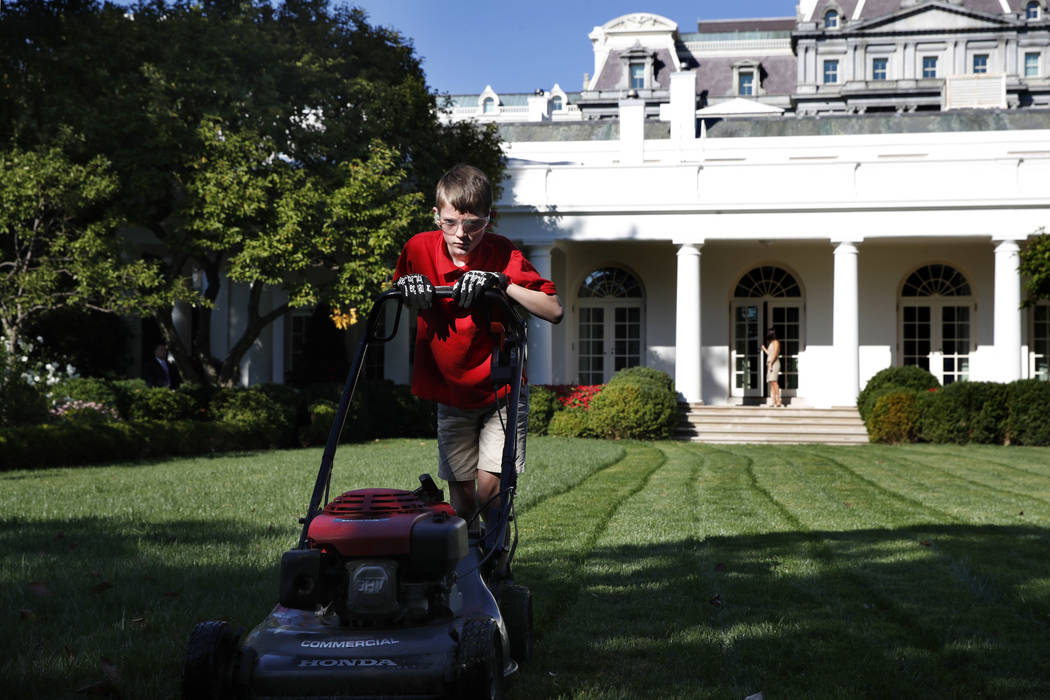 Frank Giaccio, 11, of Falls Church, Virginia, is focused as he mows the lawn of the Rose Garden, Friday, Sept. 15, 2017, at the White House in Washington. The 11-year-old wrote President Donald Tr ...