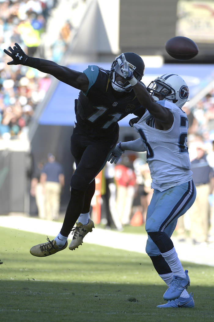 Jacksonville Jaguars wide receiver Marqise Lee (11) and Tennessee Titans cornerback Brice McCain battle for a pass during the second half of an NFL football game in Jacksonville, Fla., Saturday, D ...