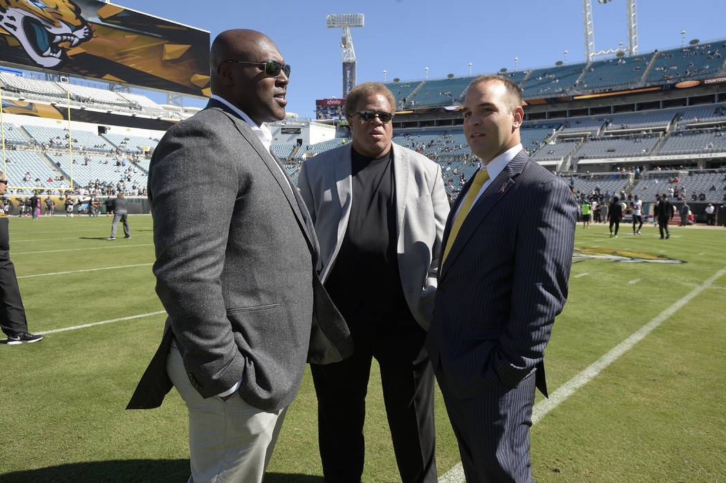 Jacksonville Jaguars general manager David Caldwell, right, chats with Oakland Raiders general manager Reggie McKenzie, center, and Joey Clinkscales, Raiders director of player personnel, before a ...