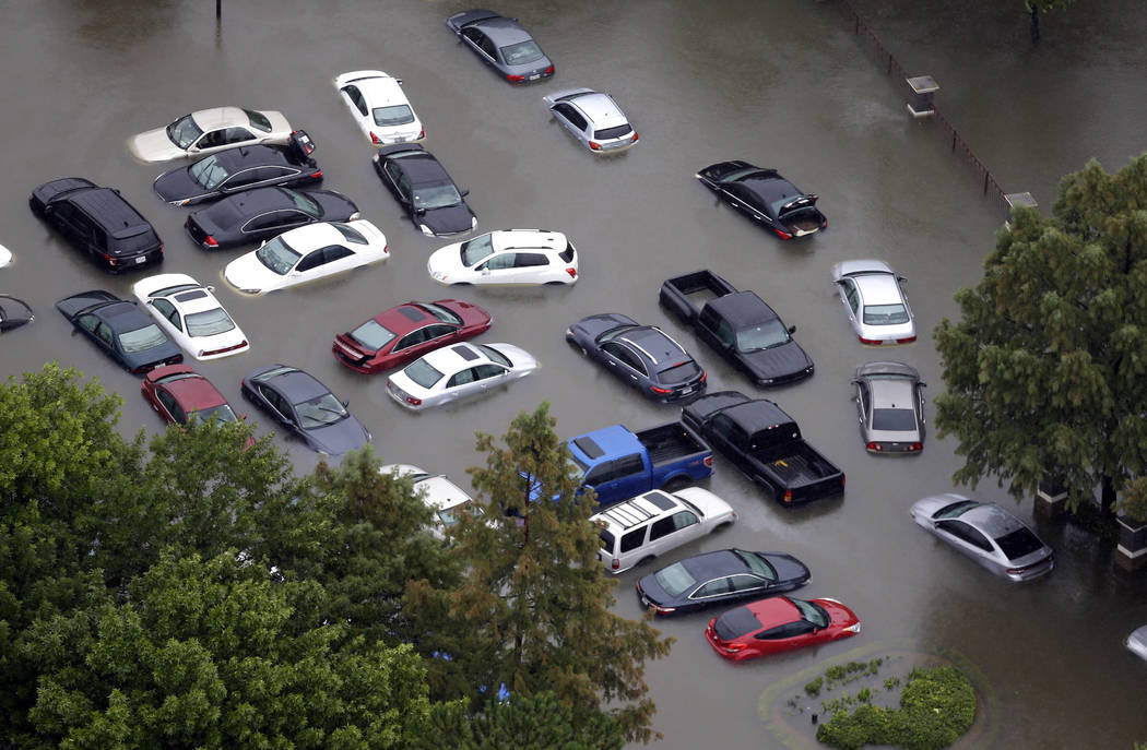 In this Aug. 29, 2017, file photo, cars are flooded near the Addicks Reservoir as floodwaters from Tropical Storm Harvey rise in Houston. (AP Photo/David J. Phillip, File)